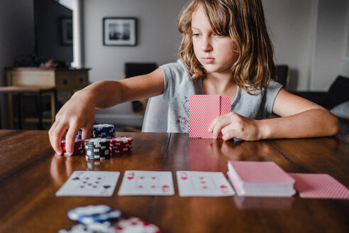 Girl playing cards at table, stacking gambling chips - ISF20037