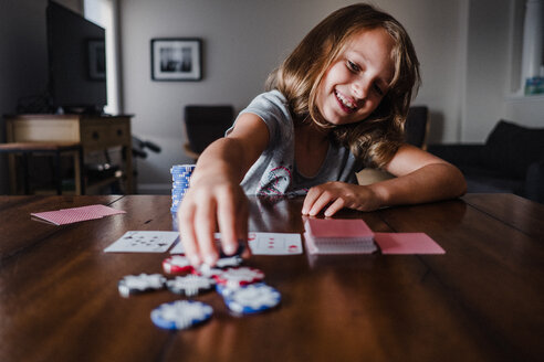 Girl playing cards at table, placing gambling chips - ISF20040
