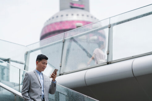 Young businessman looking at smartphone on city stairway, Shanghai, China - ISF20070