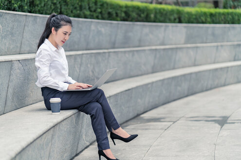 Young businesswoman typing on laptop on city seat, Shanghai, China - ISF20073