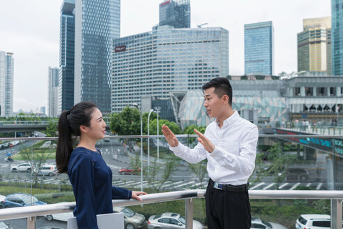 Young businesswoman and man talking on balcony in city financial district, Shanghai, China - ISF20076