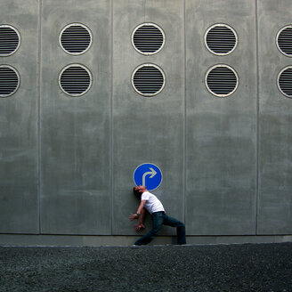 Full length side view of a man posing under a road sign - INGF03929