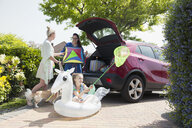 Lesbian couple and daughter loading kite and inflatable unicorn into car hatchback in sunny driveway - CAIF22191