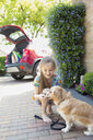 Girl giving treat to dog in driveway - CAIF22206