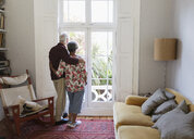 Affectionate, serene senior couple looking out living room window - CAIF22221