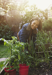 Portrait smiling active senior woman gardening - CAIF22227