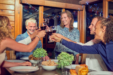 Friends celebrating, drinking red wine and enjoying dinner in cabin - CAIF22239
