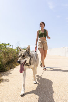 Young woman going walkies with her dog on promenade - WPEF01073