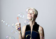 Portrait of smiling woman watching soap bubbles - FLLF00043