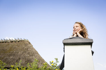 Girl lying on a wall under blue sky - OJF00264