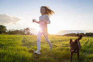 Girl with a dog running over a field at sunset - OJF00270