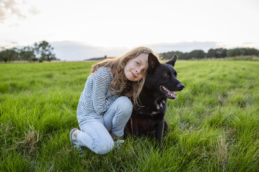 Girl with a dog sitting on a field - OJF00273