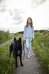 Girl with a dog standing on a field path - OJF00276