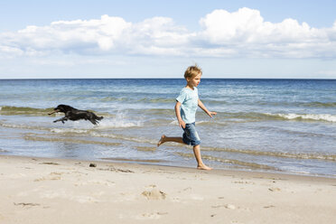 Boy with dog running at the beach - OJF00279
