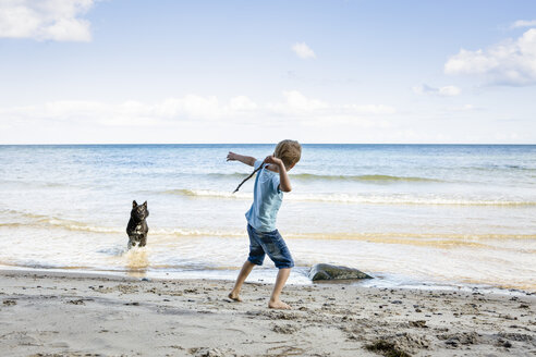 Boy playing with dog at the beach - OJF00282