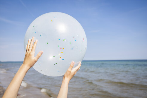 Hands of a girl holding a balloon at the beach - OJF00285