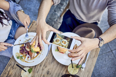 Overhead view of couple taking photo of food at outdoors restaurant - BSZF00800