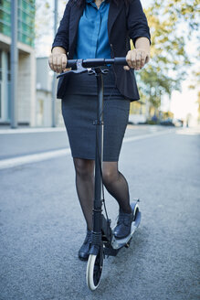 Close-up of businesswoman with scooter on the road - ZEDF01691