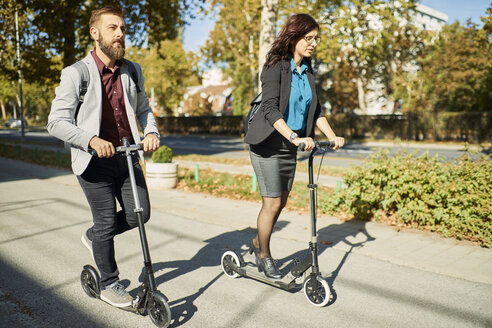 Businessman and businesswoman riding scooter - ZEDF01694