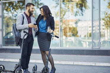 Smiling businessman and businesswoman with scooters talking on pavement - ZEDF01700