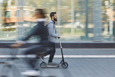 Businessman riding scooter along office building - ZEDF01712