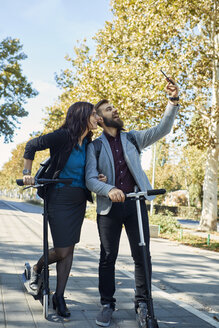 Happy business couple with scooters taking a selfie - ZEDF01718