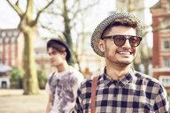 Teenage boy wearing sunglasses in park - LUXF01788