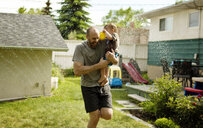 Cheerful father carrying son while playing in sprinkler at backyard - CAVF51463