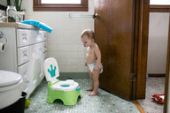 Shirtless baby girl looking at potty while standing in bathroom - CAVF51481
