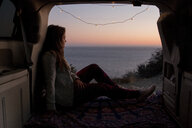 Thoughtful woman looking at view while sitting in pick-up truck against sea during sunset - CAVF51484