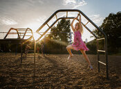 Girl hanging on monkey bars against sky at playground during sunset - CAVF51511
