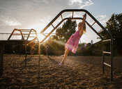 Side view of girl hanging on monkey bars against sky at playground during sunset - CAVF51514
