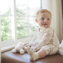 Cute baby boy looking away while sitting on sofa against window - CAVF51556