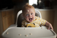 Portrait of cute baby boy playing with breakfast cereal while sitting on high chair - CAVF51559