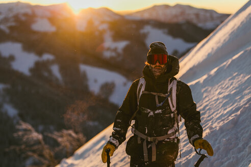 Man in ski-wear standing on snow covered mountain during sunset - CAVF51580
