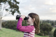 Side view of girl looking through binoculars while standing at park against cloudy sky - CAVF51583