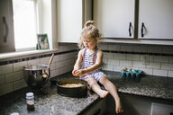 Girl preparing food in container while sitting on kitchen counter - CAVF51592