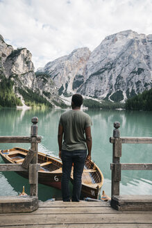 Man looking at view while standing by wooden railing by lake against mountains - CAVF51703