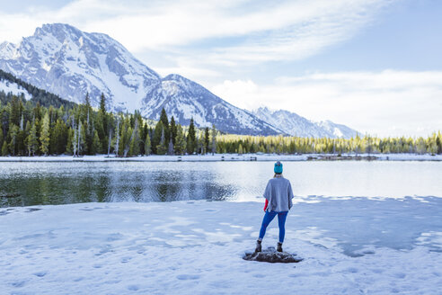 Rear view of woman standing on rock amidst frozen lake against mountains during winter - CAVF51709