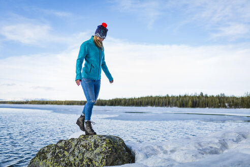 Full length of woman standing on rock amidst frozen lake against sky - CAVF51712