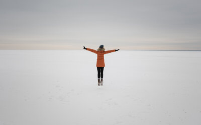 Rear view of woman with arms outstretched standing on snow covered landscape against cloudy sky - CAVF51721