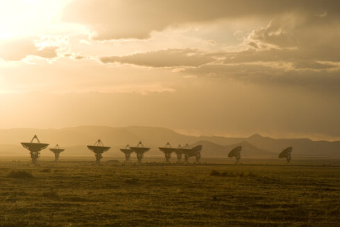 Satellite dish on field against cloudy sky during sunset - CAVF51793