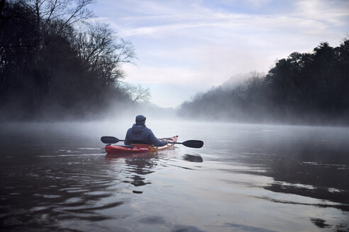 Rear view of man kayaking on Chattahoochee River against cloudy sky - CAVF51802