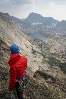 High angle view of female hiker with mountain climbing equipment standing on cliff against sky - CAVF51862