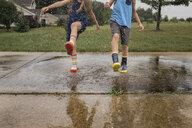 Low section of siblings splashing water at footpath - CAVF51868