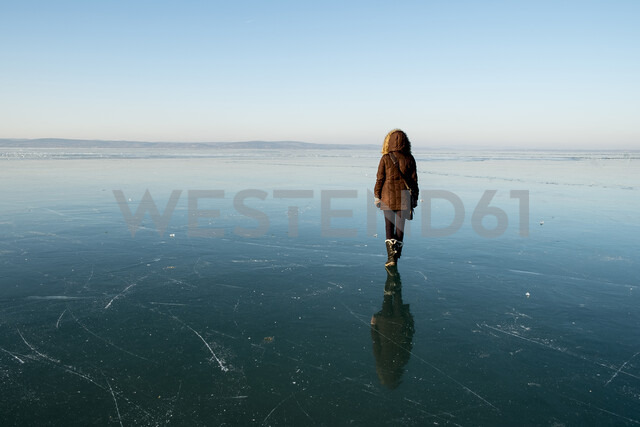 Rear view of woman in warm clothing standing at beach against sky during sunset - CAVF51889 - Cavan Images/Westend61