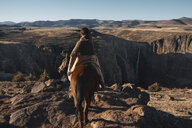 Rear view of woman riding horse on mountain against clear sky - CAVF51946