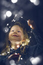 Happy girl playing with illuminated string lights during night - CAVF51958