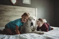 Siblings playing with Great Pyrenees on bed at home - CAVF51964
