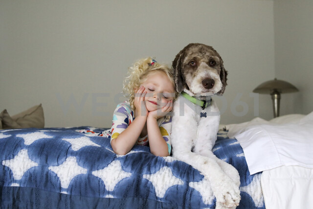 Girl with eyes closed and hands on chin lying by dog on bed against wall - CAVF51967